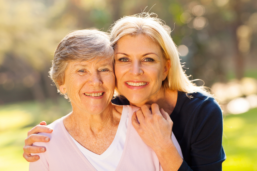 smiling senior woman and middle aged daughter outdoors closeup p